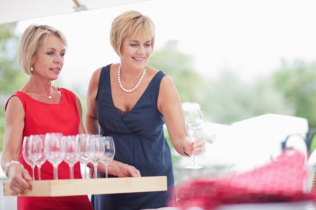 Women in evening gowns handing out wine glasses