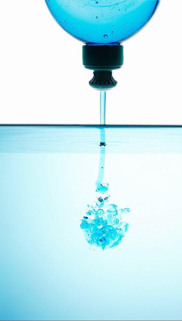 Blue washing-up liquid running into water
