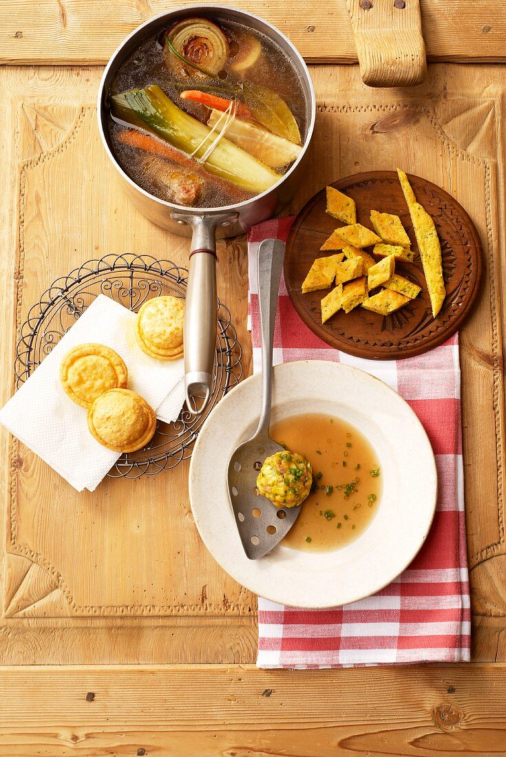 Clear fish stock, Biskuit-Käseschöberl (cheese sponge soup accompaniments), Tirteln (deep-fried pastries from South Tyrol) filled with quark and bacon dumplings
