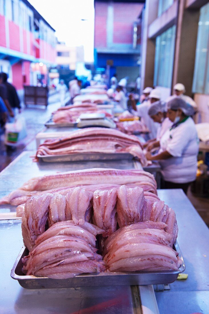 Fillets of fish and workers at a fish market, Peru
