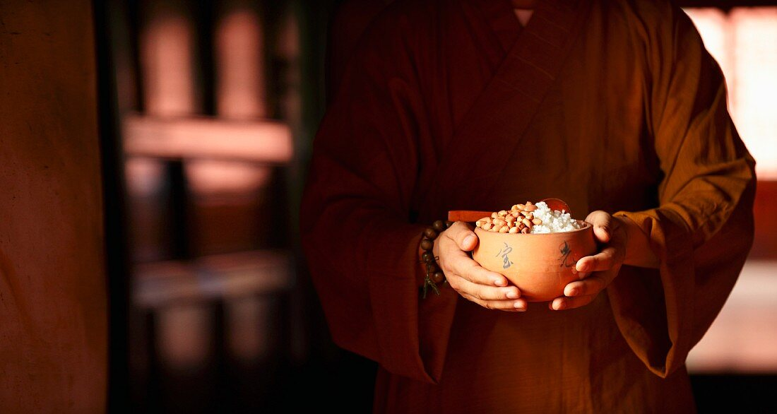 A Chinese monk with a bowl of food