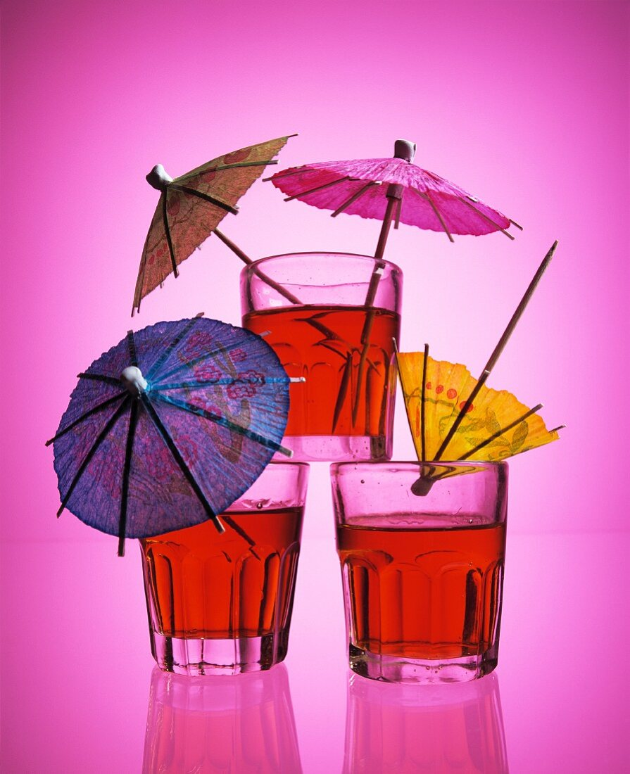 Three drinks with cocktail umbrellas against a pink background