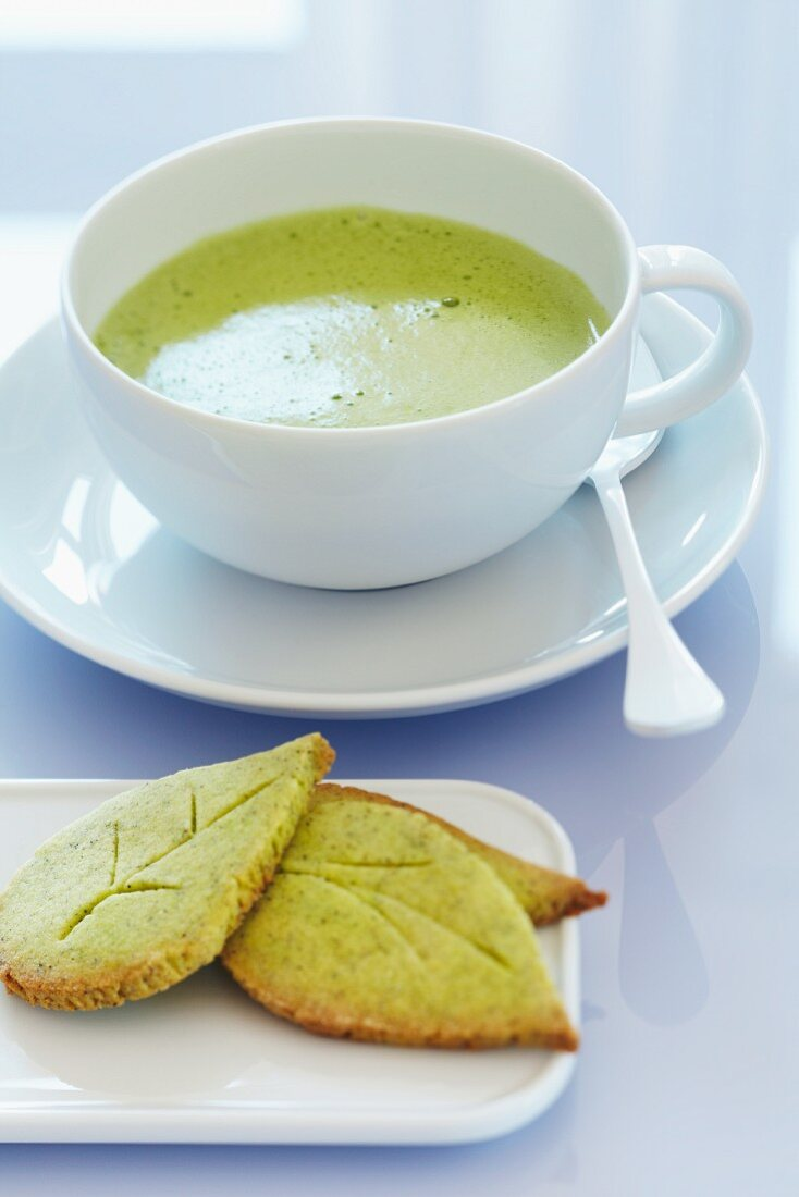 A cup of matcha tea with leaf-shaped matcha biscuits