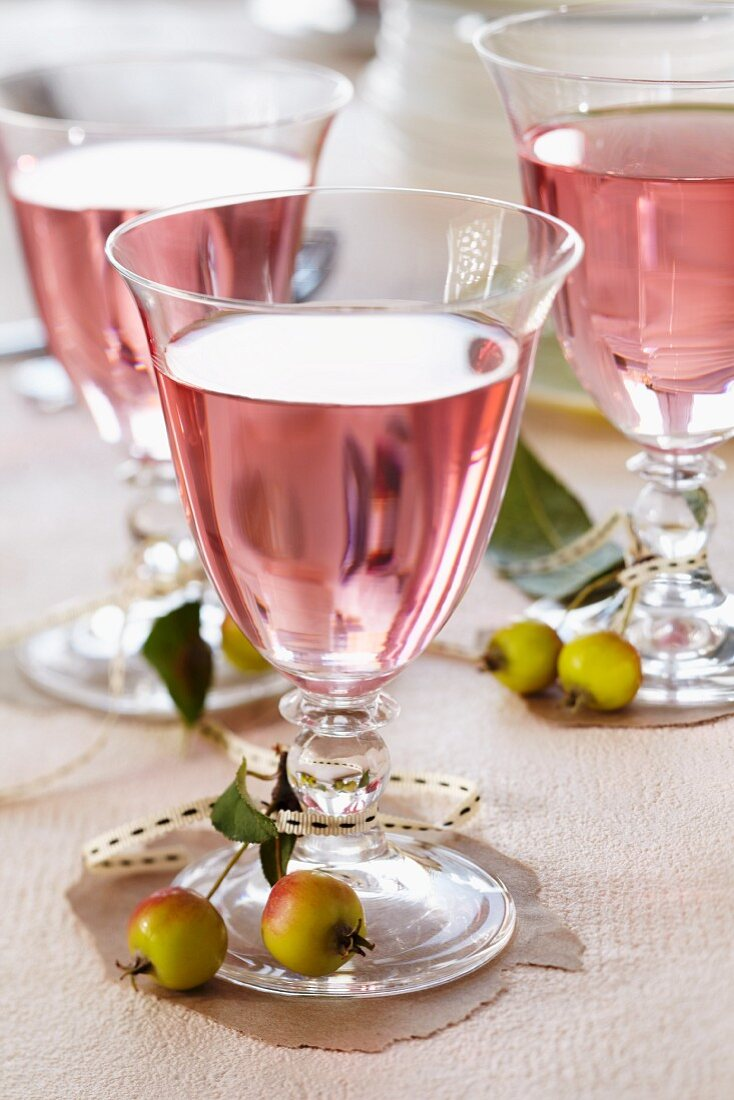 Glasses of rosé wine decorated with ornamental apples