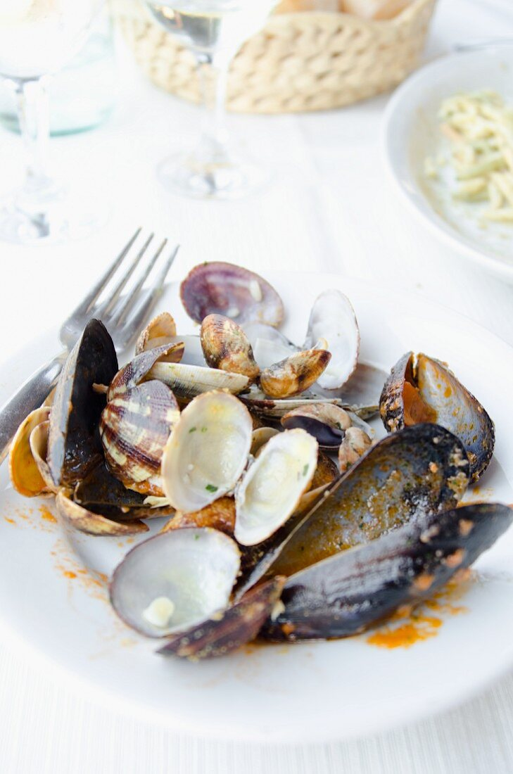 The remains of clams and mussels on a porcelain plate, with wine glasses and a bread basket