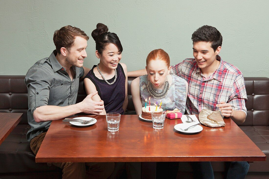 Four friends celebrating birthday in restaurant