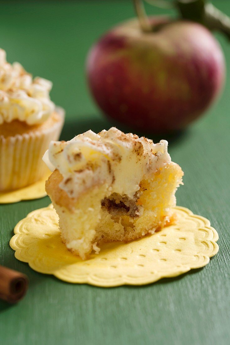 A cupcake with apple and cinnamon filling and buttercream icing
