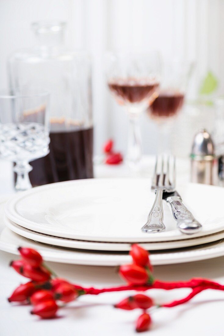 A place setting with white plates and silver cutlery on an autumnal table