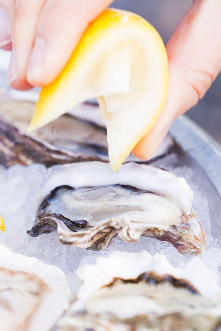 Fresh Lemon Being Squeezed Over Oysters on the Half Shell