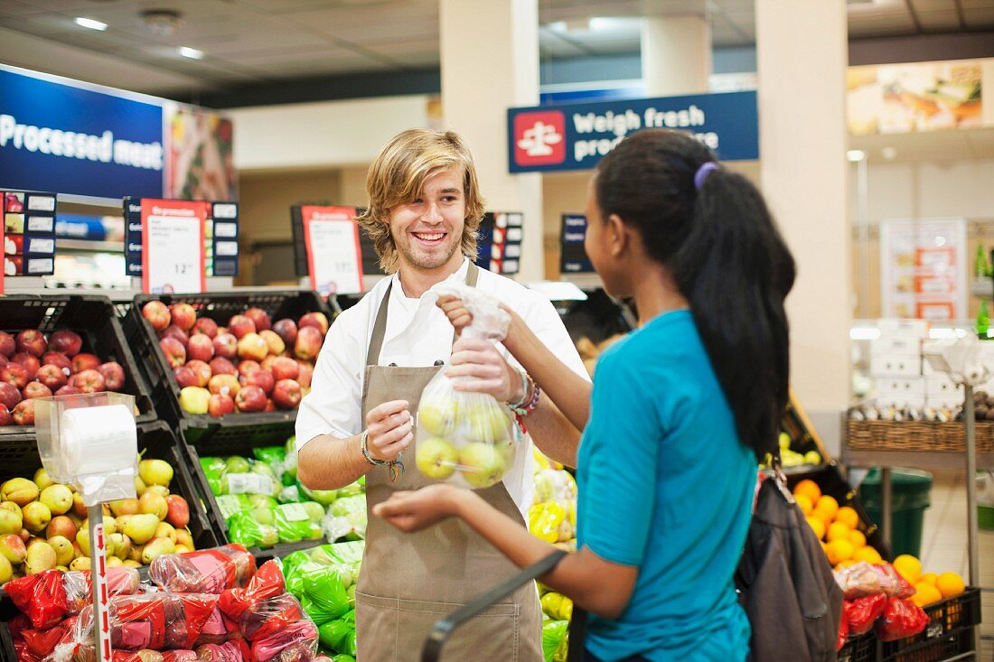 Young male sales assistant handing apples to customer