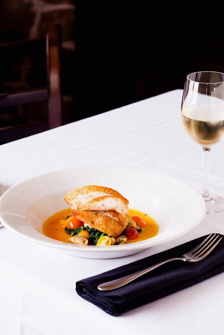 Halibut Served over Greens with a Clam Sauce and Cherry Tomatoes in a White Bowl; Served with a Glass of White Wine