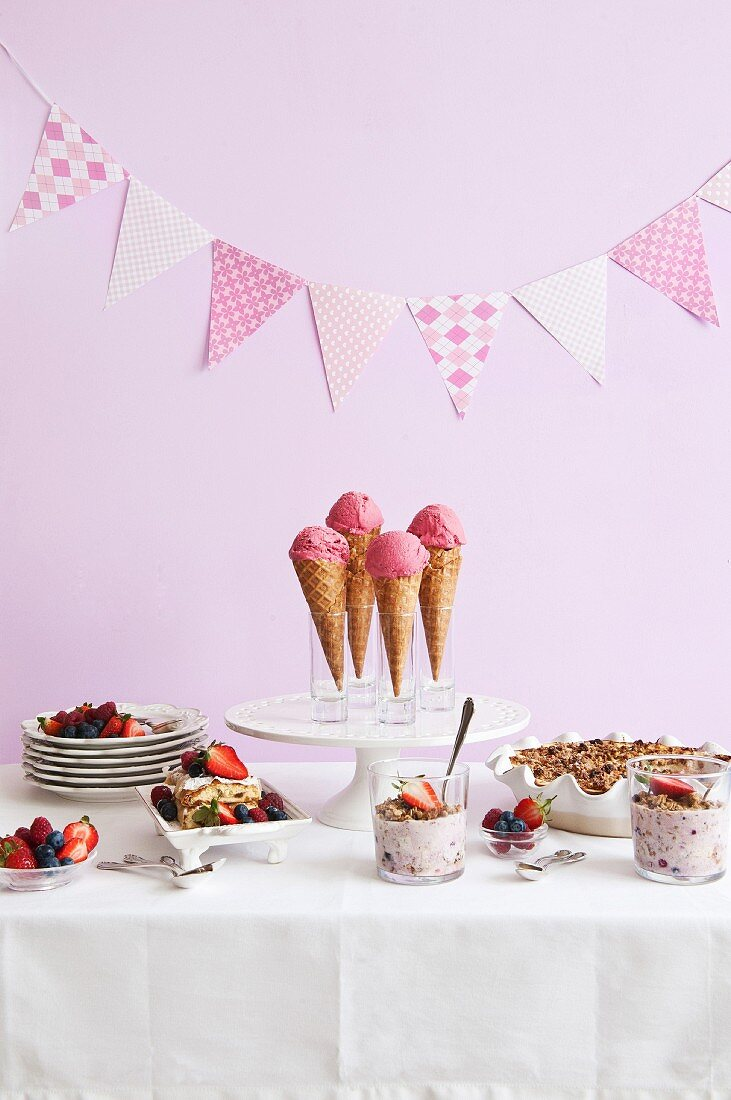 A dessert buffet with ice cream cones, berries and cakes