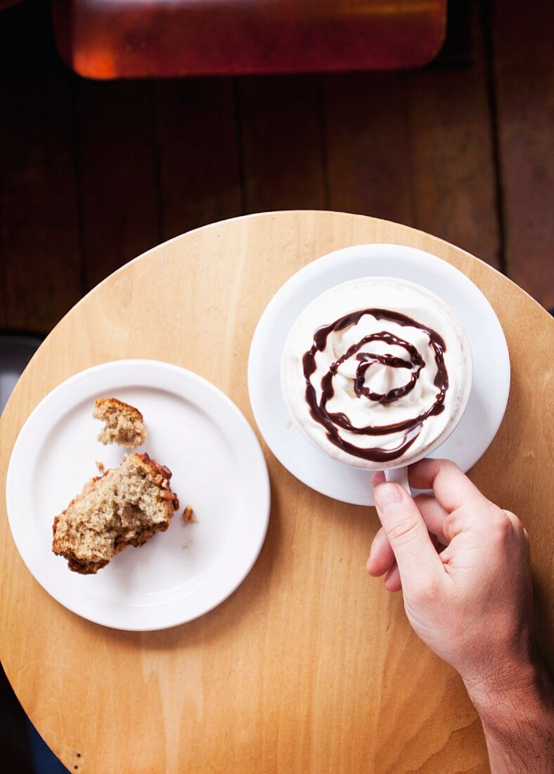 A hand holding a cup of hot chocolate, with a piece of banana and nut muffin to one side