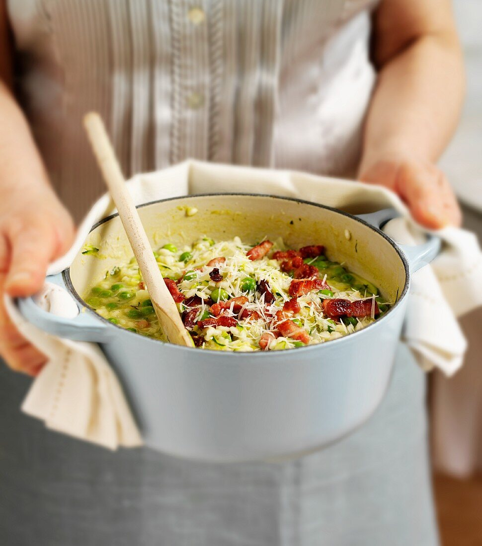 A woman holding a casserole pot full of courgette and pea risotto