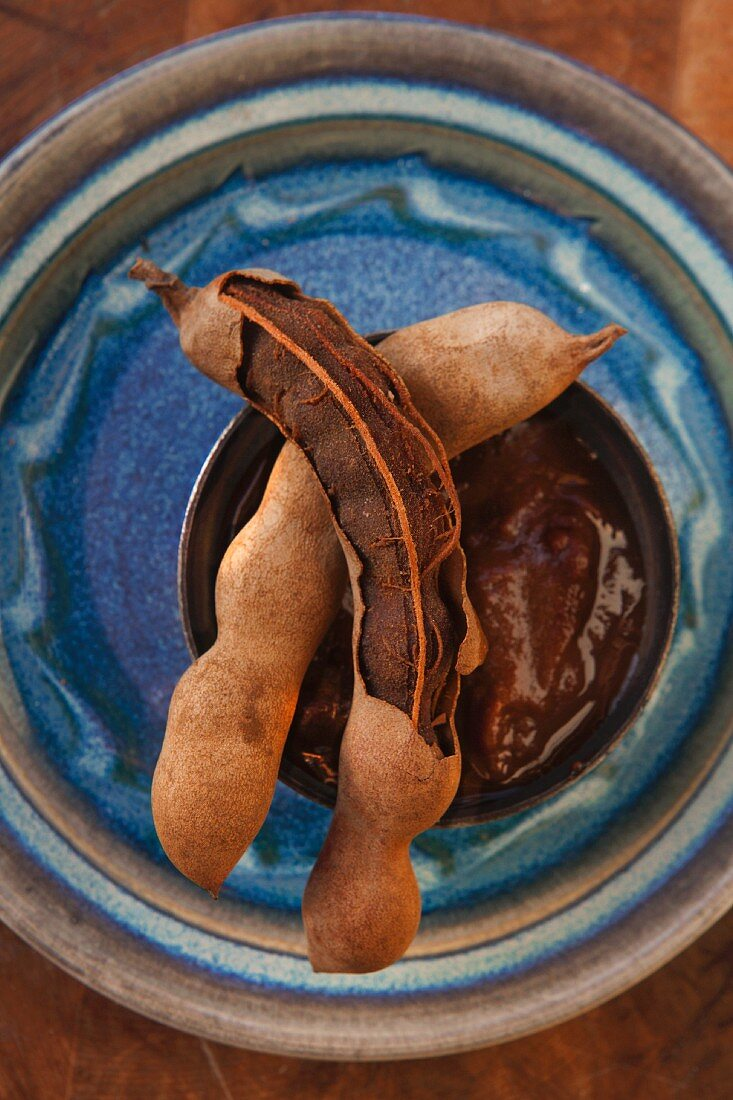 Fresh tamarinds and tamarind paste in a small bowl