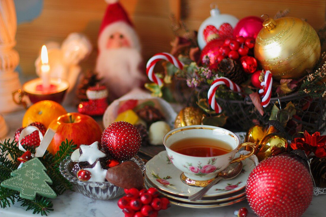 A cup of tea with a rose pattern, Christmas biscuits and Christmas decorations