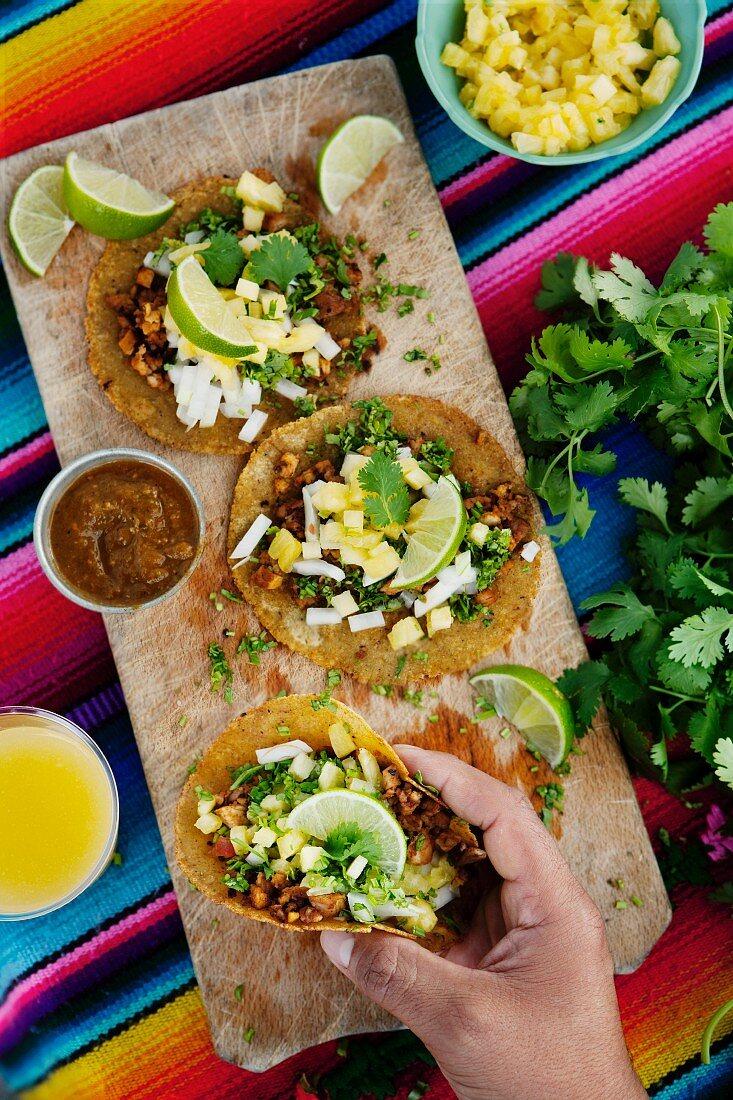 A hand holding a taco al pastor (corn tortillas with pork, Mexico)
