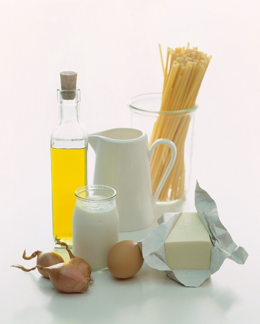 A still life of foodstuffs featuring milk, yoghurt, oil, pasta, an egg and butter