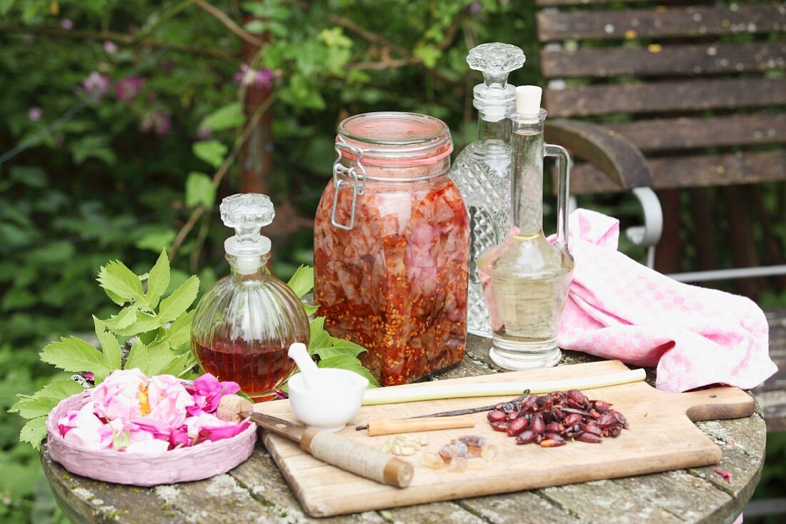 Homemade rose liqueur made from petals and fruits in a glass, balloon-shaped carafe and steeping in a flip-top jar