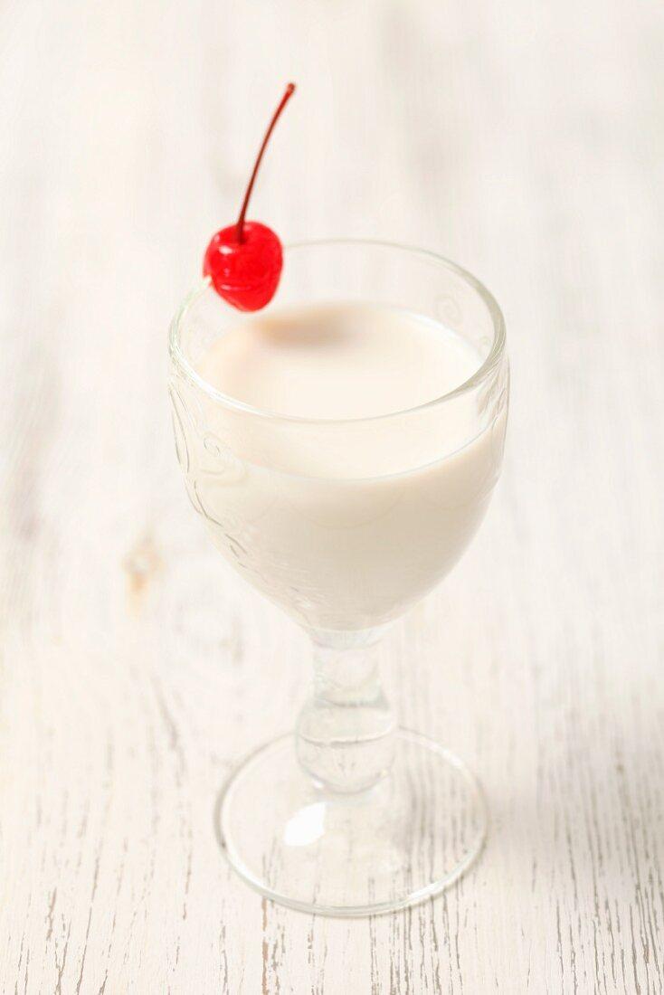 Coconut liqueur with milk and a glacé cherry