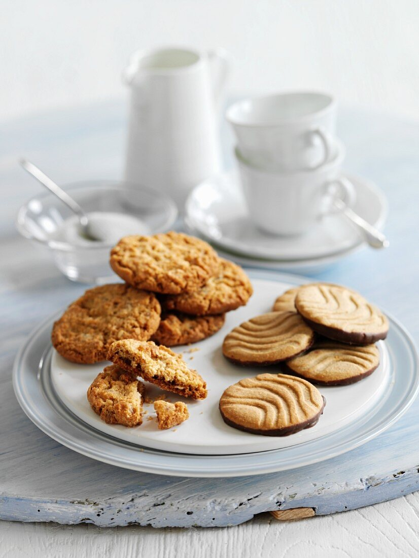 Handmade cookies, coffee cups, a small jug and a bowl of sugar