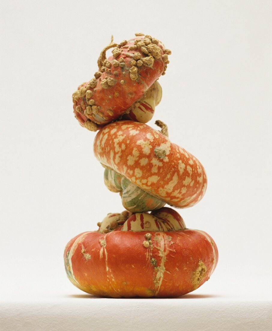 Three turban squash stacked on on top of the other