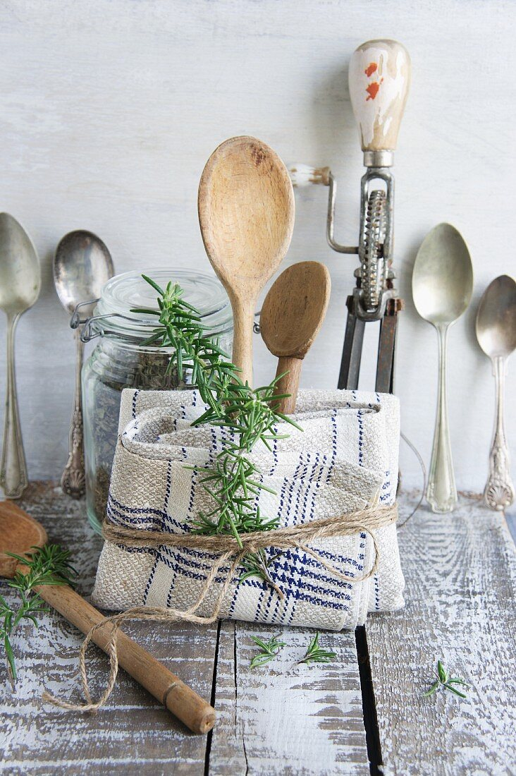 Old kitchen utensils: spoons, beater, wooden spoon and linen dish towel