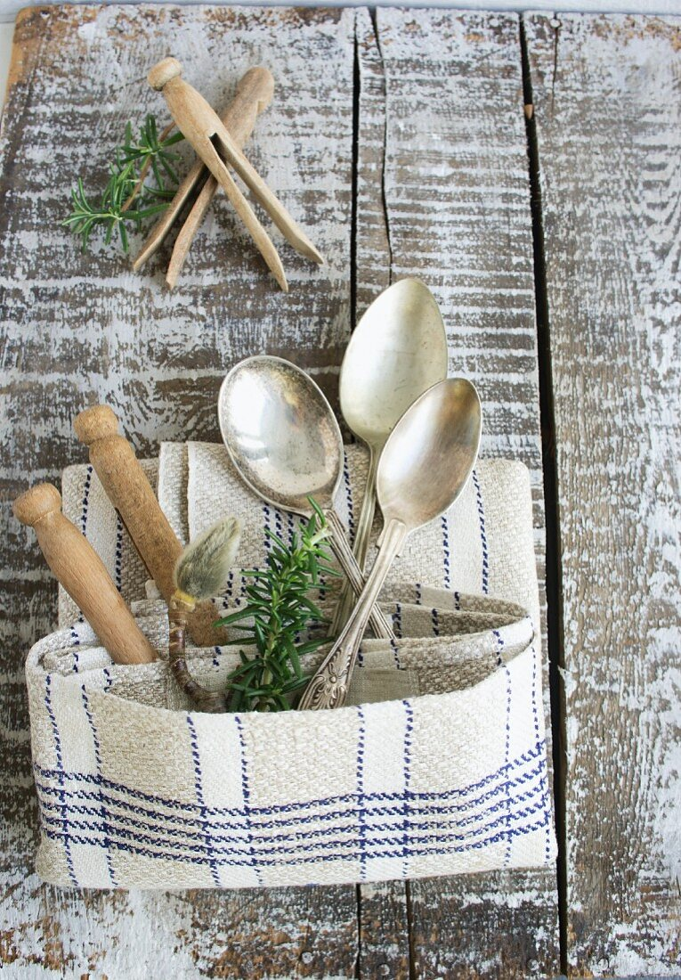 Silver spoons and wooden clothes pins in a pocket made from a linen dish towel