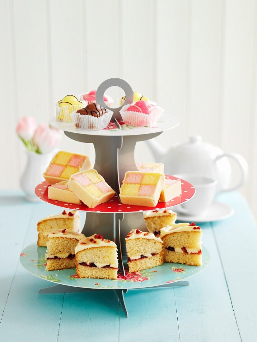 A tiered cake stand with petit fours, Battenburg cake and Victoria Sponge cake (England)