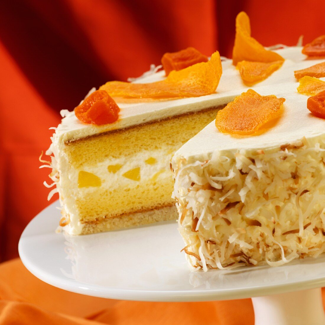 Pineapple Cream Cake Topped with Dried Mango and Papaya with Toasted Coconut; Slice Removed