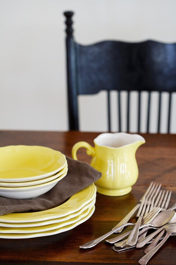 Yellow plates, bowls, milk jug and cutlery on a wooden table