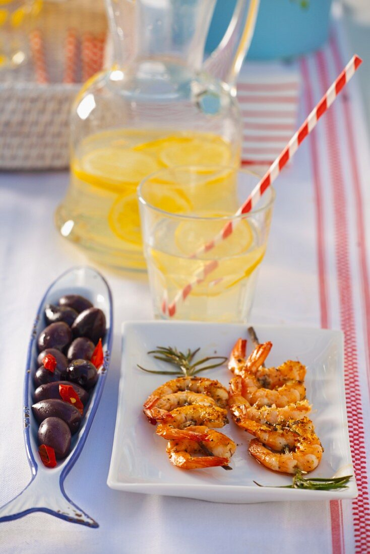 Herb and prawn skewers and black olives with peppers