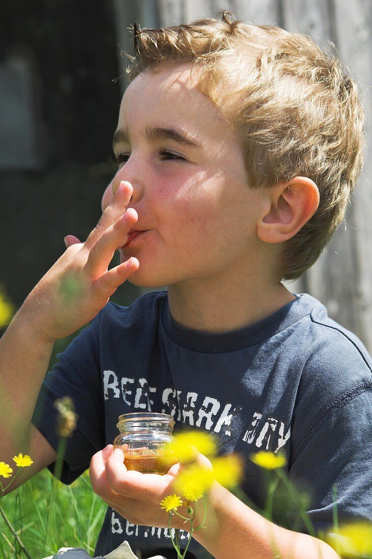 A boy tasting freshly bottled wild honey