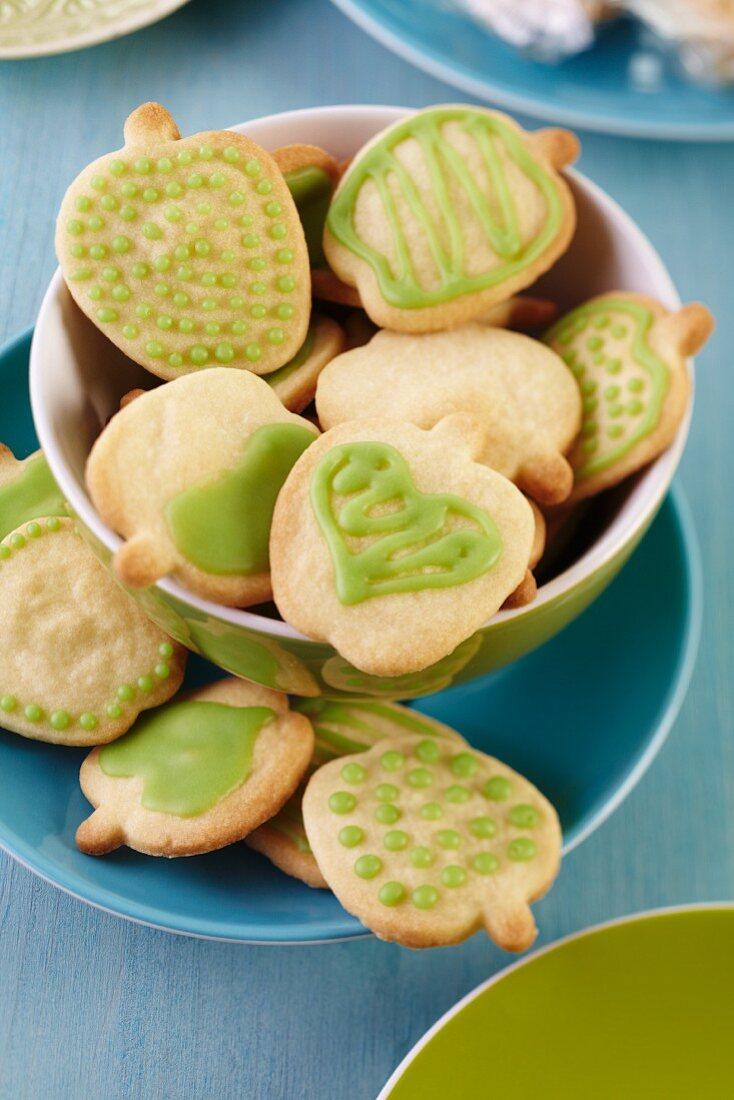 Apfelförmige Kekse mit grüner Zuckerglasur in einer Schale