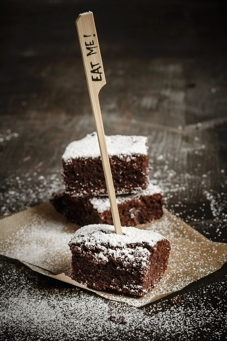 Three brownies on brown paper dusted with icing sugar and an Eat Me sign