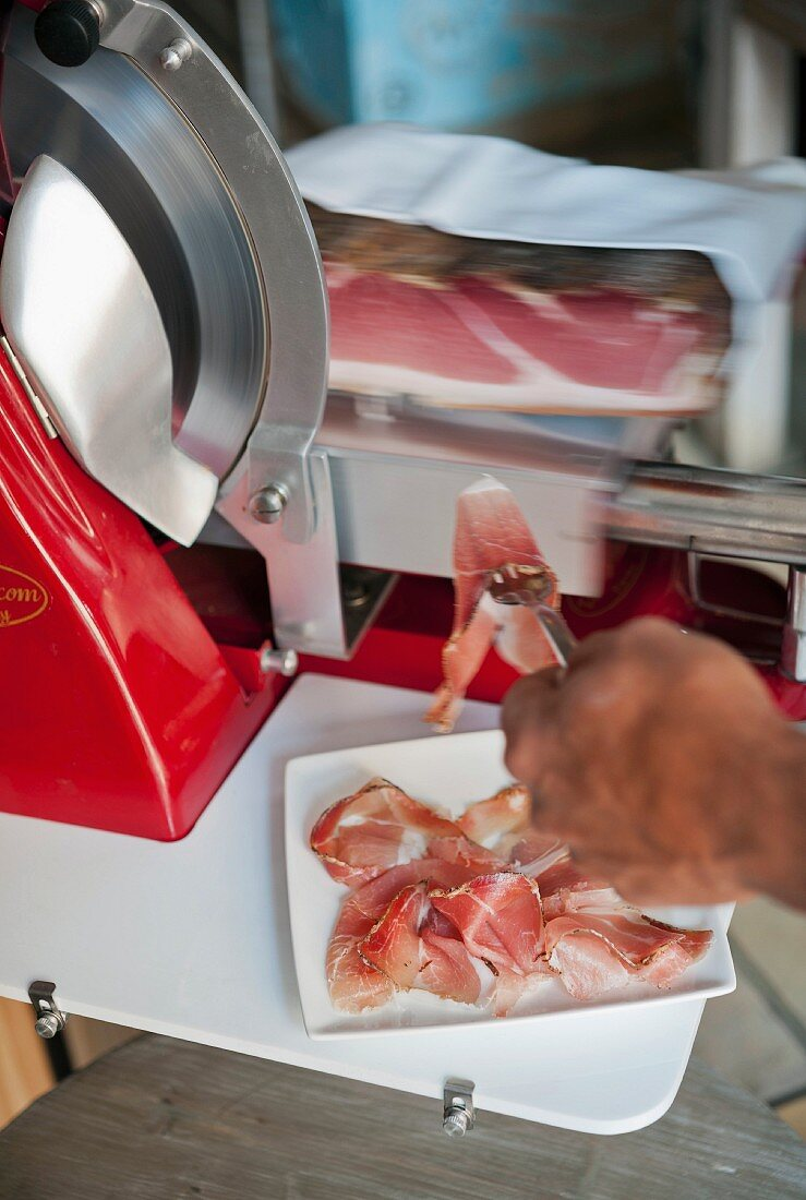 Prosciutto being sliced wafer thin by a slicing machine