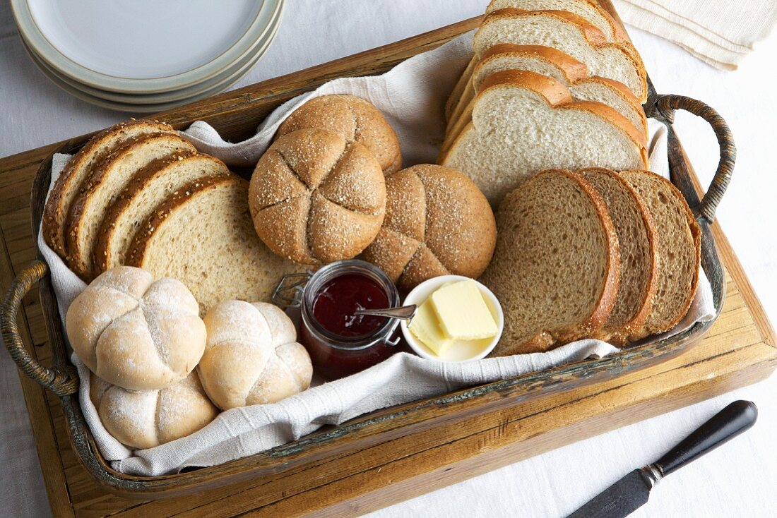 Basket of mixed breads and rolls with jam and butter