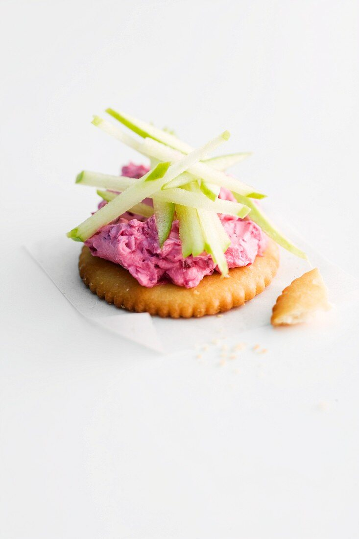 A cracker topped with beetroot and apple