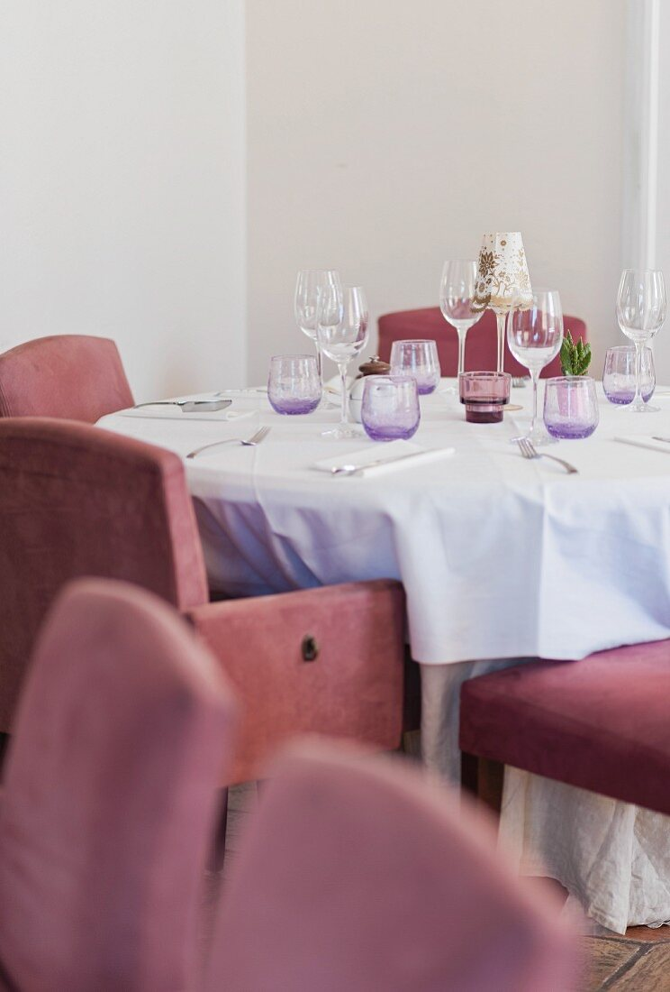 A table laid for a meal in a restaurant with cushioned chairs upholstered in old rose