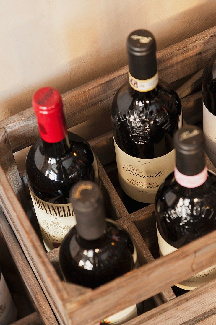 Assorted bottles of red wine in a wooden crate