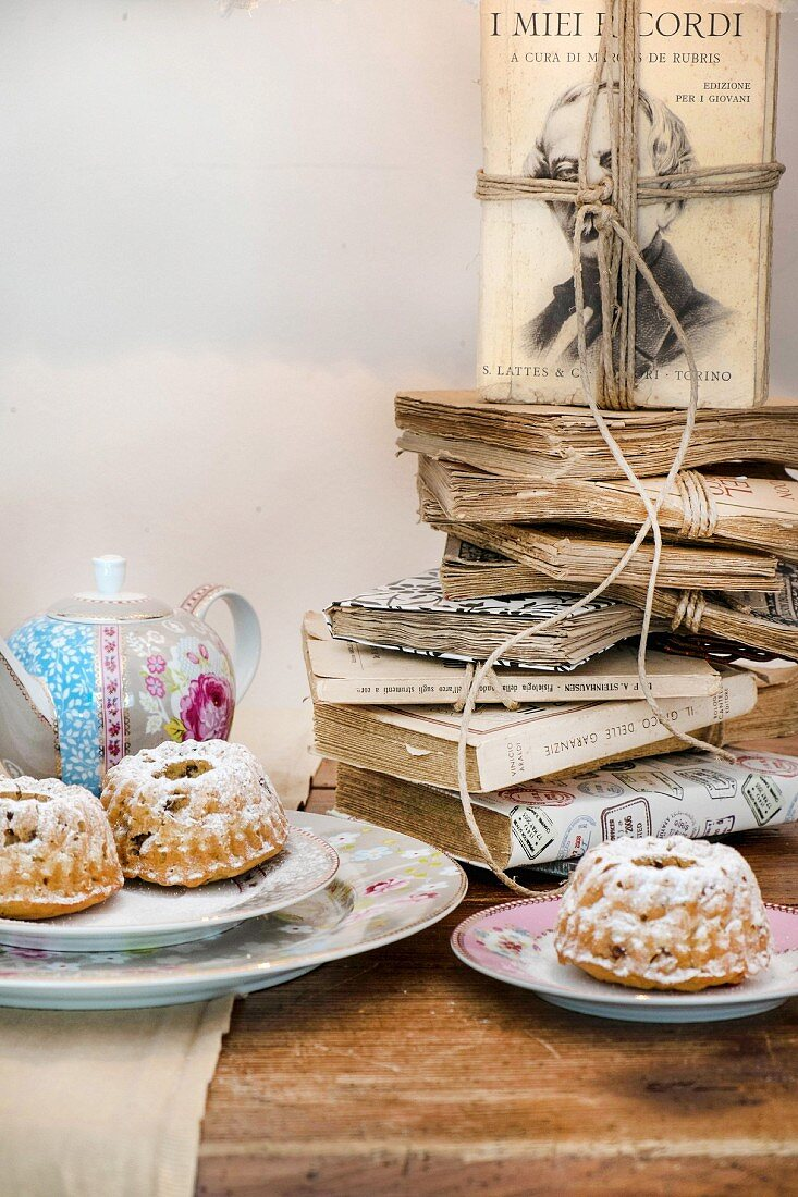 Old books stacked on table set with small bundt cakes