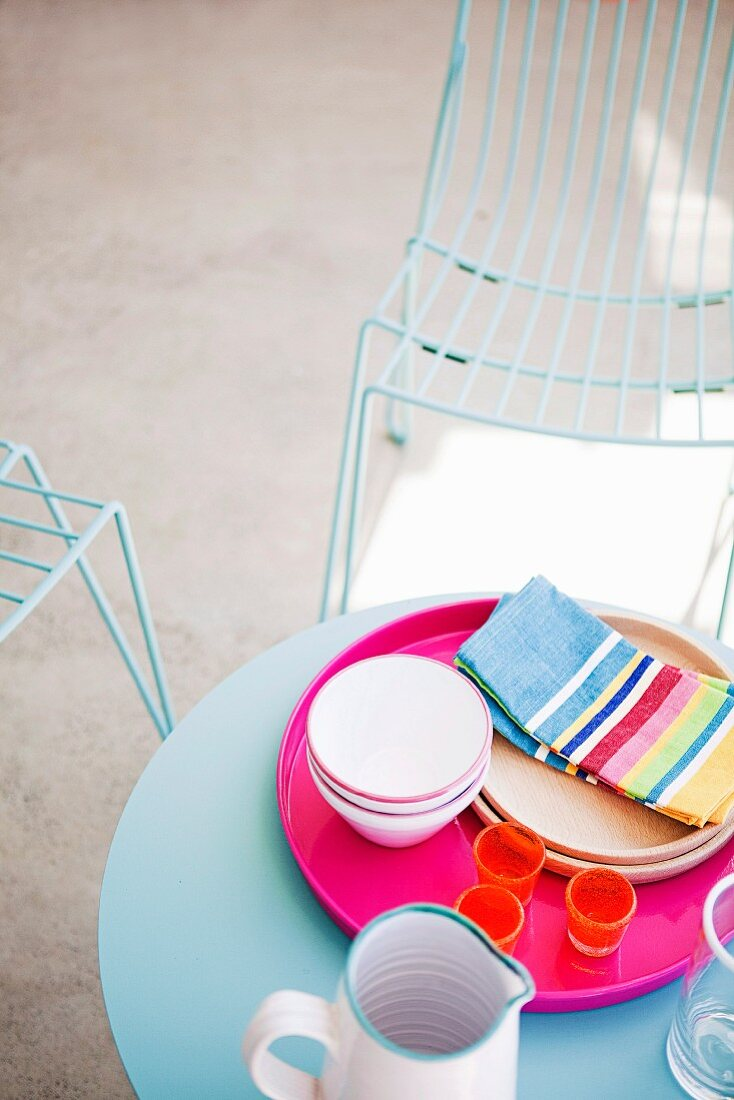 Pink tray of crockery on round blue terrace table and delicate wire mesh chairs in background