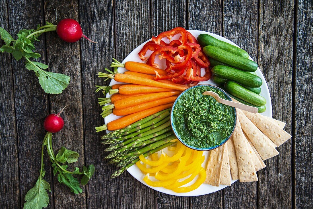 A plate of raw vegetables with a herb dip and crispbread
