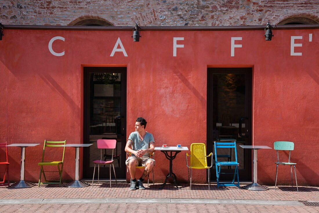 A young man sitting outside a caf
