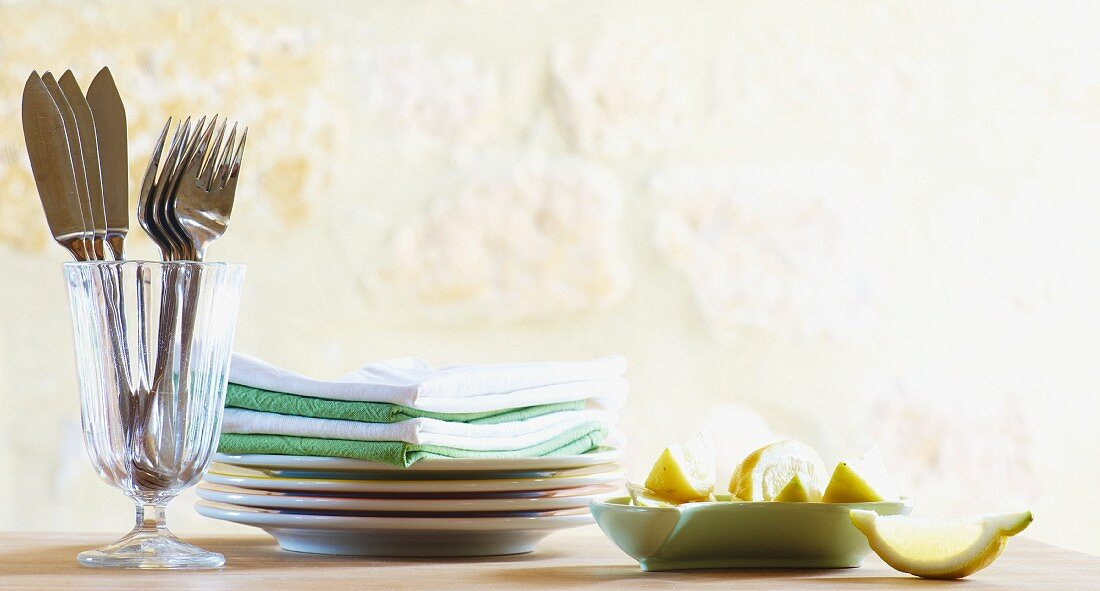 Cutlery in a glass, stacked plates and napkins; lemon wedges to one side