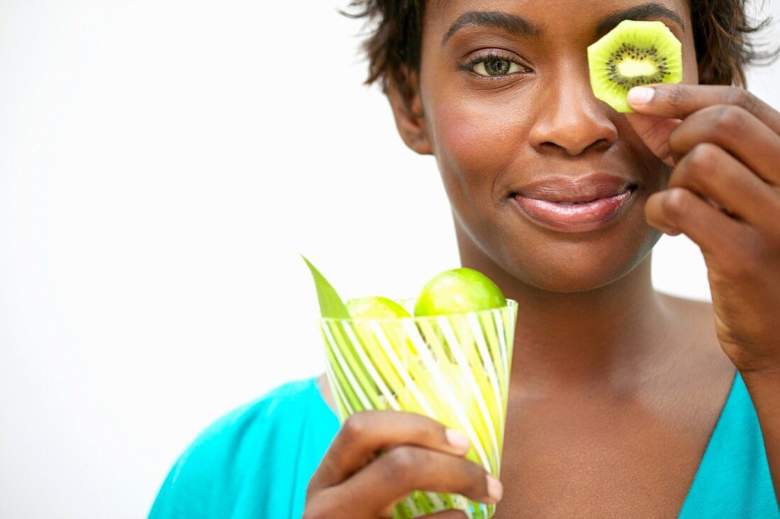 Woman holding kiwi slice in front of eye