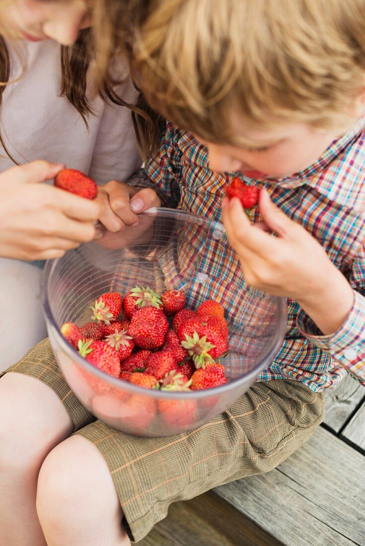Boy and girl eating strawberry