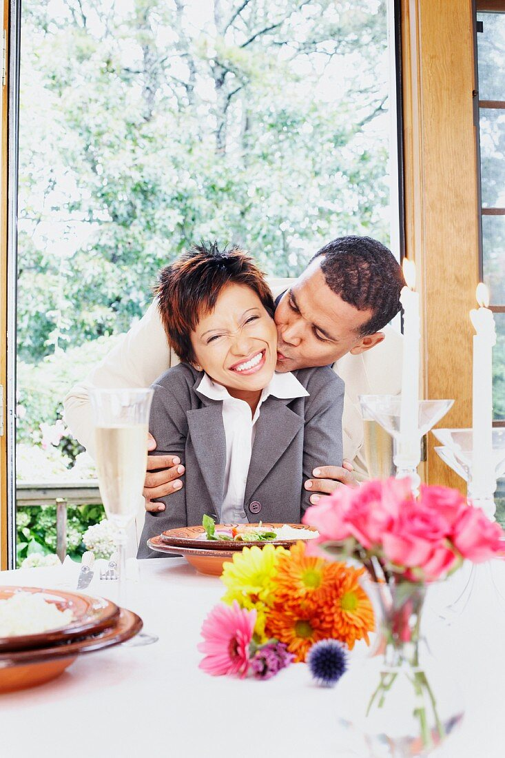 Couple kissing at the dinner table