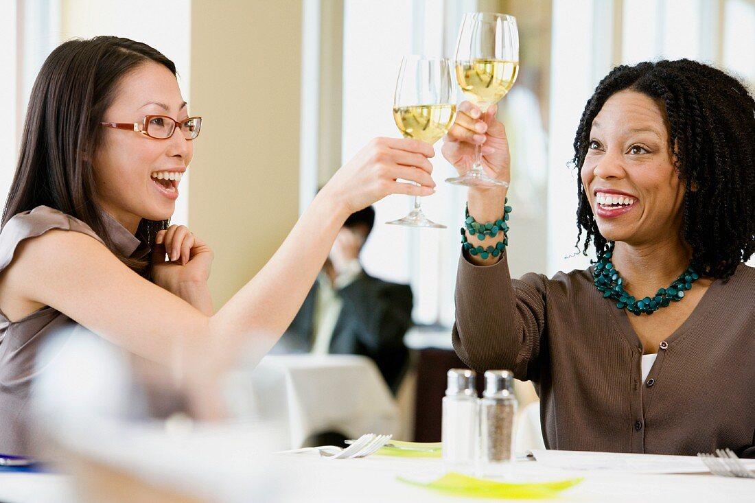 Two businesswomen toasting in restaurant