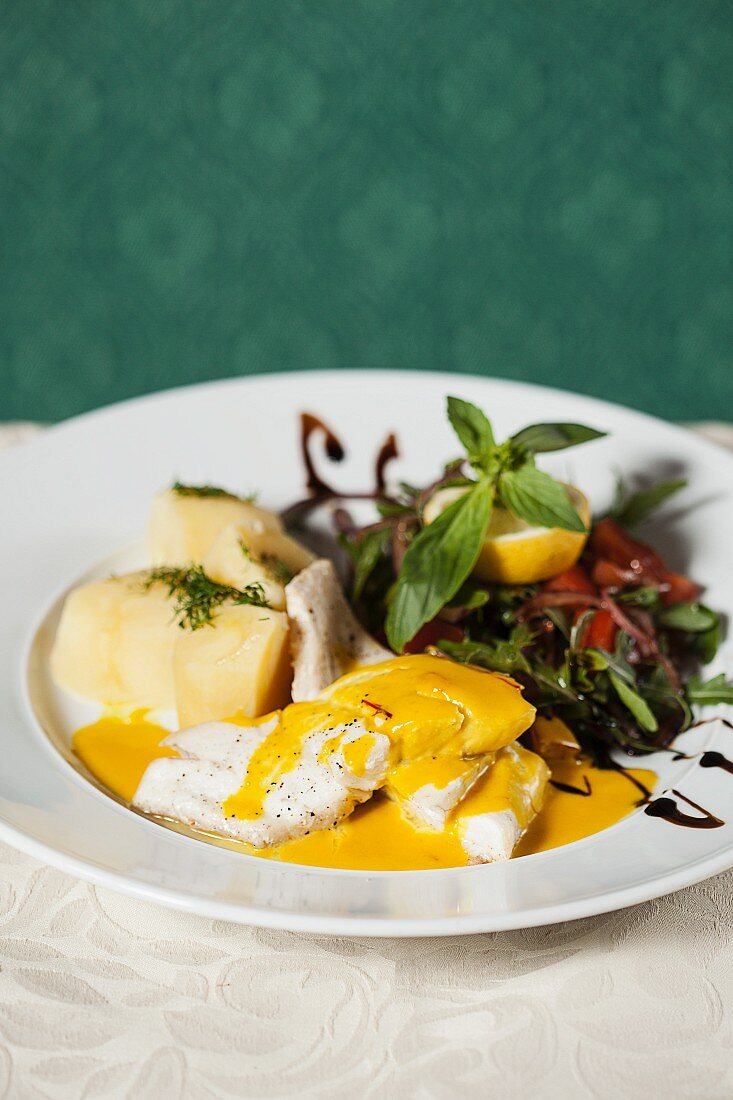 Zander fillet in saffron sauce with potatoes and salad